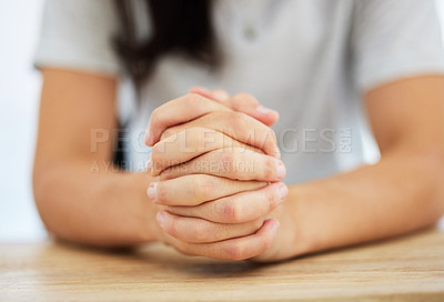 Buy stock photo Shot of an anonymous woman sitting at a table with her hands clasped together