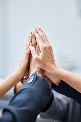 Buy stock photo Shot of a team of colleagues high fiving in solidarity