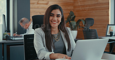 Buy stock photo Shot of young businesswoman sitting at her desk using her laptop in her office