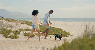 Buy stock photo Shot of a young couple spending the day at the beach with their dog