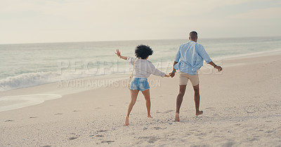 Buy stock photo Shot of an affectionate couple walking on the beach
