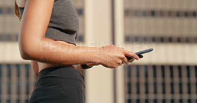 Buy stock photo Cropped shot of an unrecognziable woman standing alone in the city and using her cellphone during a workout
