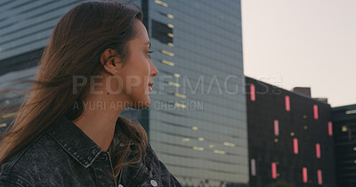Buy stock photo Cropped shot of an attractive young woman looking thoughtful while standing outside in the city