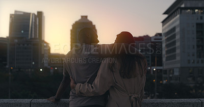 Buy stock photo Rearview shot of an affectionate young couple taking in the views while standing outside in the city