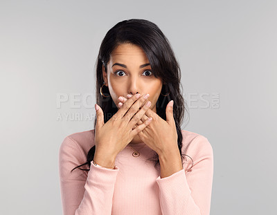 Buy stock photo Shot of a beautiful young woman looking surprised while standing against a grey background