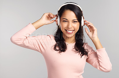 Buy stock photo Shot of a beautiful young woman wearing headphones while standing against a grey background