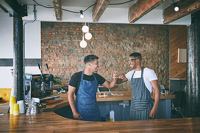 Buy stock photo Shot of two confident young men giving each other a fist bump while working in a cafe