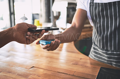 Buy stock photo Shot of an unrecognisable man using a smartphone to make a payment in a cafe