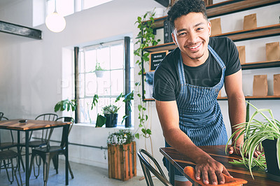 Buy stock photo Shot of a young wiping a table while working in a cafe