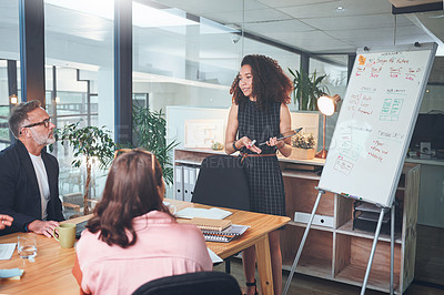 Buy stock photo Shot of a young businesswoman using a digital tablet delivering a presentation to her coworkers in a modern office
