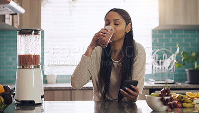 Buy stock photo Shot of a young woman enjoying her morning smoothie in her kitchen at home