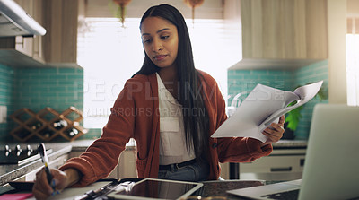 Buy stock photo Shot of a young businesswoman working form home going over paperwork in her kitchen at home