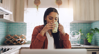 Buy stock photo Shot of a young businesswoman drinking a cup of coffee while working fat home