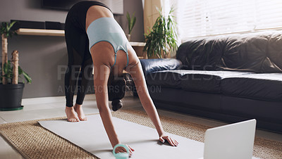 Buy stock photo Shot of a young woman practising a yoga routine at home
