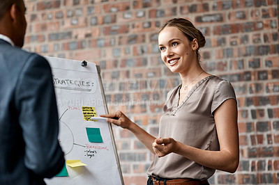 Buy stock photo Shot of an attractive young businesswoman standing with a coworker and using a visual aid for a presentation