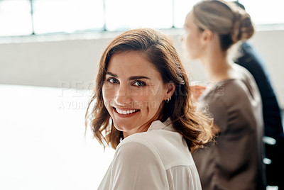 Buy stock photo Shot of an attractive young businesswoman sitting with her coworkers during a meeting in the office