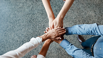Buy stock photo High angle shot of a group of unrecognisable businesspeople joining their hands together in a huddle