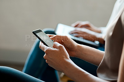 Buy stock photo Cropped shot of an unrecognizable businesswoman sitting and using her cellphone in the office
