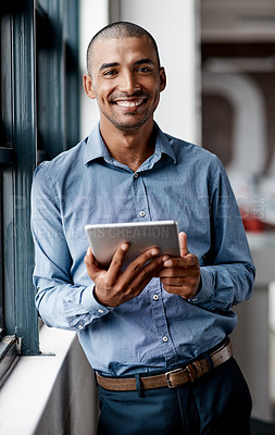Buy stock photo Shot of a handsome young businessman standing alone in the office and using a digital tablet