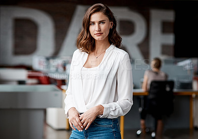 Buy stock photo Shot of an attractive young businesswoman standing alone in the office during the day