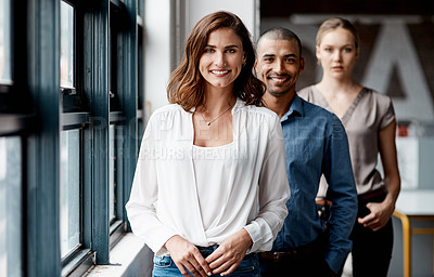 Buy stock photo Shot of a diverse group of businesspeople standing in a line behind each other in the office during the day