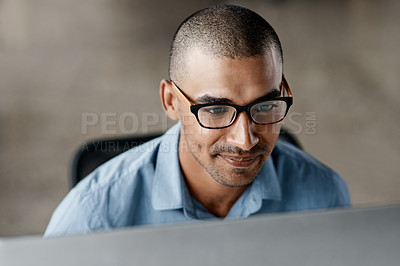 Buy stock photo Shot of a handsome young businessman sitting alone in the office and using his computer
