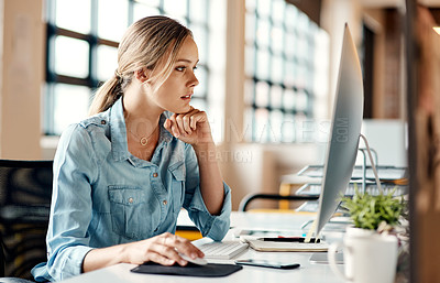 Buy stock photo Shot of an attractive young businesswoman sitting alone in the office and looking contemplative while using her computer
