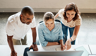 Buy stock photo High angle shot of a group of businesspeople working together on a computer in an office