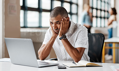 Buy stock photo Shot of a young businessman looking bored while working on a laptop in an office
