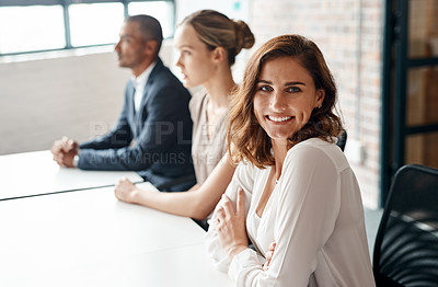 Buy stock photo Portrait of a young businesswoman sitting in an office with her colleagues in the background