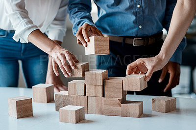 Buy stock photo Closeup shot of a group of unrecognisable businesspeople stacking building blocks together in an office