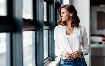 Buy stock photo Shot of a confident young businesswoman looking thoughtfully out a window in an office