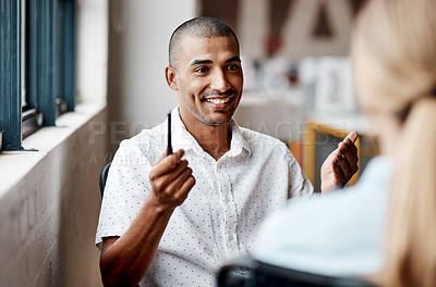 Buy stock photo Shot of a young businessman having a discussion with a colleague in a modern office