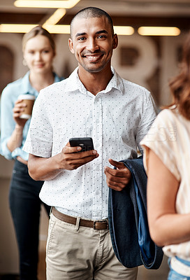 Buy stock photo Shot of a young businessman using a smartphone while waiting in line in a modern office