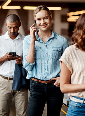 Buy stock photo Shot of a young businesswoman using a smartphone while waiting in line in a modern office