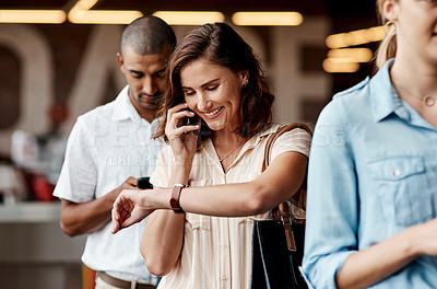 Buy stock photo Shot of a young businessman using a smartphone and checking the time while waiting in line in a modern office