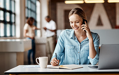 Buy stock photo Shot of a young businesswoman using a laptop, smartphone and making notes in a modern office