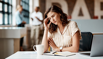 Buy stock photo Shot of a young businesswoman looking stressed out while using a laptop in a modern office
