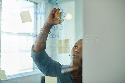 Buy stock photo Shot of an attractive young businesswoman standing in the office and using a transparent board and sticky notes to plan