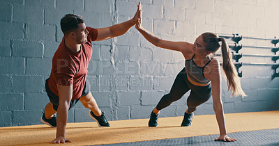 Buy stock photo Shot of two people giving each other a high-five while doing push ups together at the gym