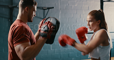 Buy stock photo Shot of a woman wearing boxing gloves while working out at the gym with her trainer