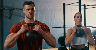Buy stock photo Shot of two people working out with kettlebells at the gym