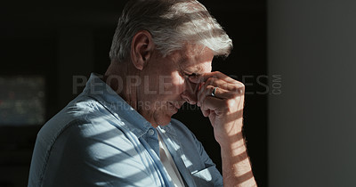 Buy stock photo Shot of a mature man standing alone in a dark room at home and feeling anxious