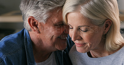Buy stock photo Shot of a mature couple sitting in their living room together and sharing an intimate moment