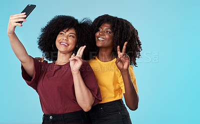 Buy stock photo Studio shot of two young women using a smartphone to take selfies against a blue background