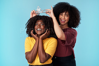 Buy stock photo Studio shot of a young woman putting a crown on her friend against a blue background