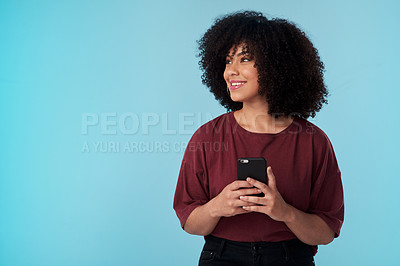 Buy stock photo Studio shot of a young woman using a smartphone against a blue background