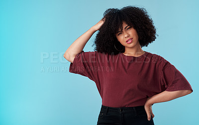Buy stock photo Studio shot of a young woman looking confused against a blue background