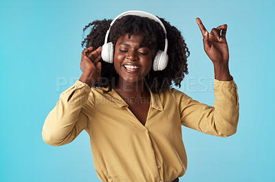 Buy stock photo Studio shot of a young woman using headphones and dancing against a blue background