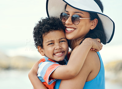 Buy stock photo Shot of a mother holding her son at the beach